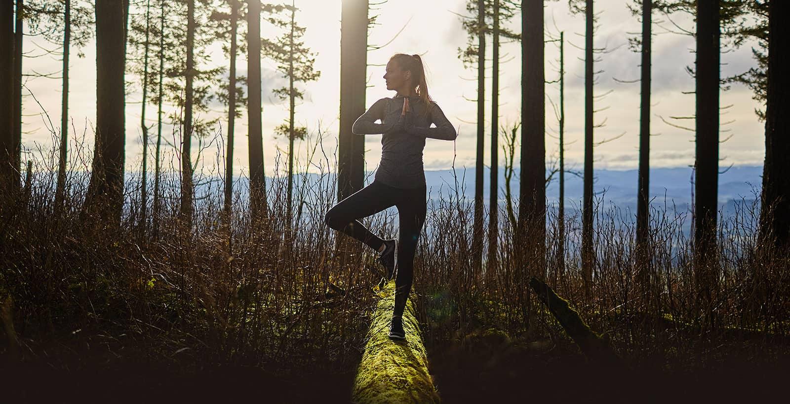 Fille qui fait du Yoga au sommet d'une montagne des Laurentides